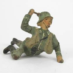 Infantry soldier lying, throwing hand grenade